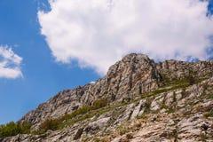 登上Chatyr Dag 在Chatyr Dag高原的狭窄的干草原谷,围拢由山坡,与表面上的云彩的阴影 免版税库存照片