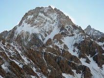 登上Dykh Tau的北部面孔看法在早晨阳光下与一个清楚的山顶, 库存照片