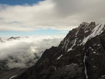 登上Dykh Tau的北部面孔看法在早晨阳光下与一个清楚的山顶, 库存图片