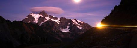 登上Mt Shuksan明亮的月亮夜汽车车灯 免版税库存图片