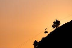 登上Srdj的空中览绳或索道在杜布罗夫尼克,以橙色天空为背景的克罗地亚 图库摄影