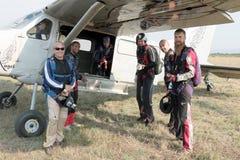 登上X328地图集天使涡轮sp的白和黑人跳伞运动员 免版税图库摄影