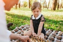下与祖父的女孩棋 免版税库存图片