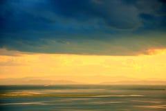 下云彩黑暗的金黄天空 免版税库存照片