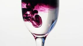滴下入杯的紫色墨水简单的水 免版税库存照片