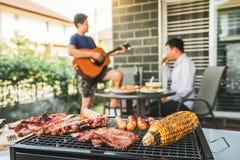 下午党享用小组的朋友喝与享受家庭党的烤肉和烤肉愉快的使用的吉他的啤酒 免版税库存照片