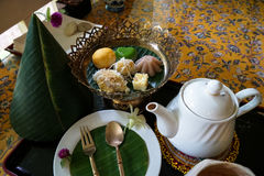 下午茶时间套与美好的香蕉叶子和花装饰的泰国传统点心在花卉样式桌布 库存照片