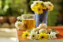 下午茶时间用中国酥皮点心和茶和花在橙色椅子 免版税库存照片
