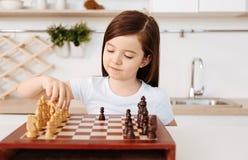 下单独棋的聪明的小女孩 免版税库存照片