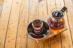 滴下咖啡杯和咖啡罐在木桌 库存照片