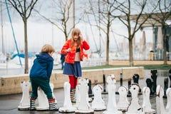 下在操场的小组两个孩子巨型棋 免版税库存照片