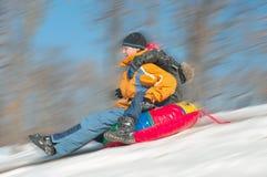 下坡一起sledding年轻人的男孩 免版税库存图片
