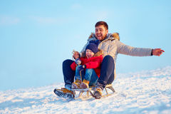 滑下坡在冬天雪的愉快的家庭 库存照片