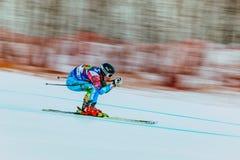 下坡竟赛者少妇在竞争中 背景在俄国杯期间的迷离作用在高山滑雪 免版税库存图片