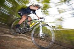 下坡mountainbiking的越野通过森林 免版税库存照片