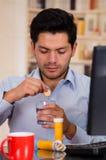 下垂在一杯的英俊的人一种药片冒泡片剂水 库存照片