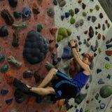下垂被包装的墙壁的登山人 库存图片