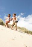 下来夫妇沙丘连续沙子年轻人 免版税库存图片