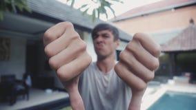 下来拇指用由年轻人的两只手,在家在庭院里,室外 分歧概念 影视素材