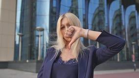 下来拇指 年轻俏丽的金发碧眼的女人在工作,看照相机 女商人的画象 t 股票视频
