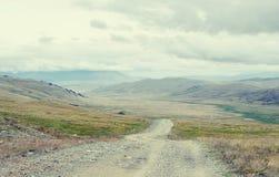 下来极端岩石路道路对从通行证的一个山谷 免版税库存照片