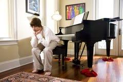 下来查找钢琴坐的长凳男孩少年 库存照片