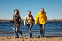 下来海滩运行三个年轻人的照相机人 图库摄影
