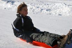 下来男孩小山害怕的sledding 库存照片