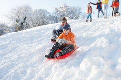 下来男孩系列小山sledging的注意的年轻人 库存照片
