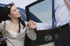 下来的商人帮助的女实业家乘汽车 免版税图库摄影