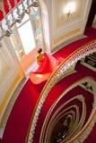 下来的庄重装束的美丽的女孩楼梯 免版税库存照片