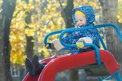 滑下来红色塑料操场的温暖的戴头巾夹克的笑的女孩滑在黄色秋天树叶子背景 库存照片