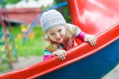滑下来红色塑料操场幻灯片的微笑的小白肤金发的女孩户外在春天 库存图片