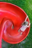 滑下来红色塑料螺旋操场幻灯片的小白肤金发的女孩顶上的射击  库存图片