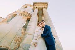 下来观点的古老大厦的背景的微笑的新婚佳偶 免版税库存图片