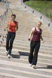 下来跑步的步骤二名妇女 免版税库存照片