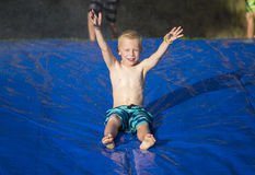 滑下来滑动和幻灯片的年轻男孩户外 免版税图库摄影