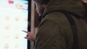移下来年轻的人站立在数字式片剂前面和  佩带在卡其色的夹克和帽子的男性侧视图 4K 股票视频