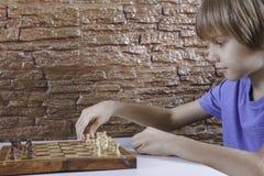 下棋和做接下来的步骤的一个小白种人男孩的画象 库存照片