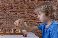下棋和做接下来的步骤的一个小白种人男孩的画象 免版税库存图片