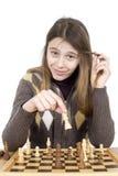 下棋和看照相机的微笑的女孩画象,她对她的接下来的步骤非常满意 免版税库存照片