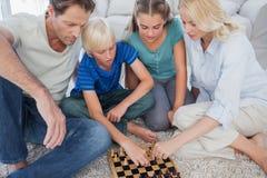 下棋的一个逗人喜爱的家庭的画象 免版税库存照片