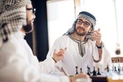 下棋的两个阿拉伯商人在桌上在旅馆客房 免版税库存照片