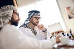 下棋的两个阿拉伯商人在桌上在旅馆客房 图库摄影