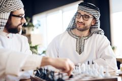 下棋的两个阿拉伯商人在桌上在旅馆客房 免版税库存图片