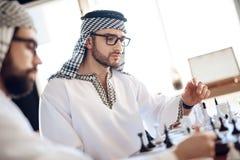 下棋的两个阿拉伯商人在桌上在旅馆客房 免版税图库摄影