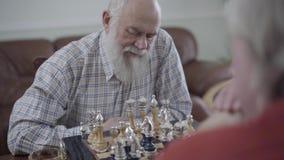 下棋的两位老人在家坐皮革沙发 认为的有胡子的人棋子采取行动 股票录像
