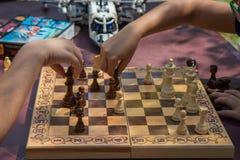 下棋的孩子在有被弄脏的玩具的庭院里在背景 图库摄影
