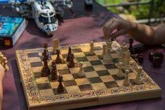 下棋的孩子在有被弄脏的玩具的庭院里在背景 免版税库存照片