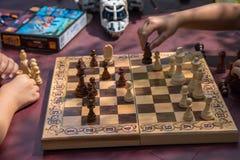 下棋的孩子在有被弄脏的玩具的庭院里在背景 免版税库存图片